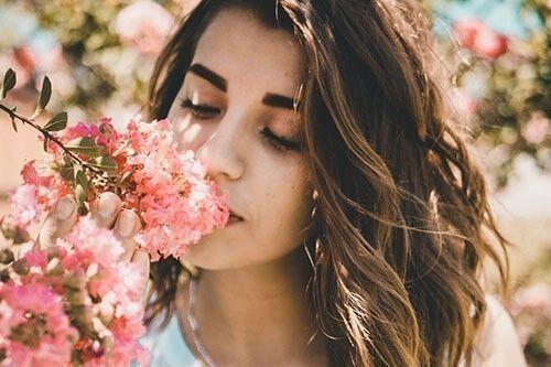 Una chica oliendo una flor