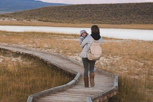 Una mujer pasea por un camino con su bebé en brazos