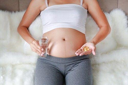 Mujer embarazada sosteniendo unas pastillas