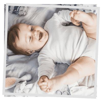 Bebé sonriendo y cogiéndose los pies